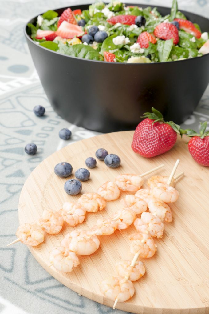 Fast prawn skewers with a fruity salad with blueberries and strawberries
